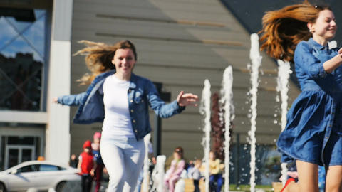 Slow Motion Happy Girls Run along Fountain Waving Hands Footage