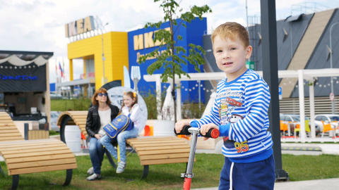 Closeup Little Boy Rides Scooter along Entertainment Park Footage