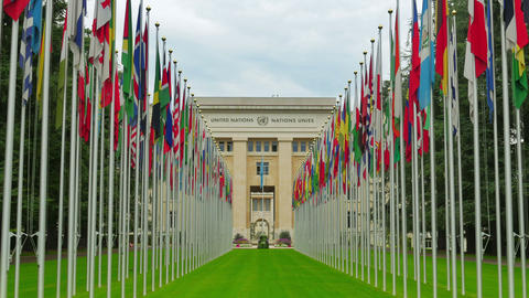 United Nations building with flags, Geneva, Switzerland, zoom out, 4K Footage