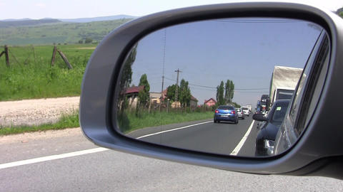 Through the rearview mirror of a car are seen as passing cars and truck on a bus Footage