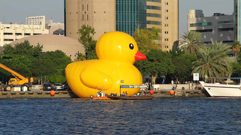 Huge yellow rubber duck on water, vibrant inflatable enlarged yellow toy Footage