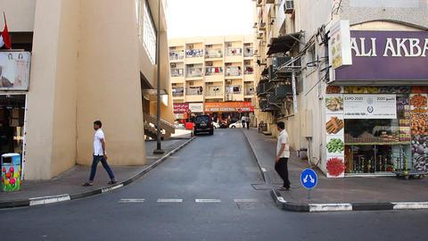Small traffic, small lane against Bur Dubai Abra Station, daytime Live Action