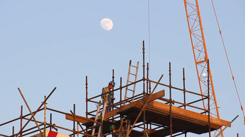 Top of scaffolds, worker climb down ladder, dusk time, telephoto lens Footage