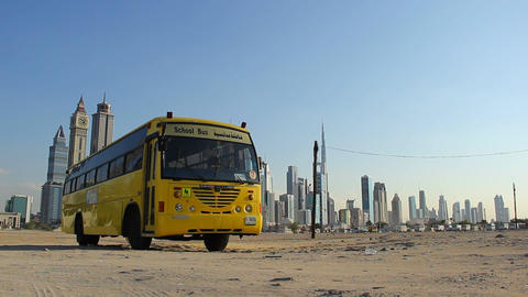 Single school bus stand at vacant sandy plot against Dubai towers on back Live Action