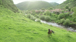Aerial: camera pan around horse and goes over beautiful old mountain village Footage