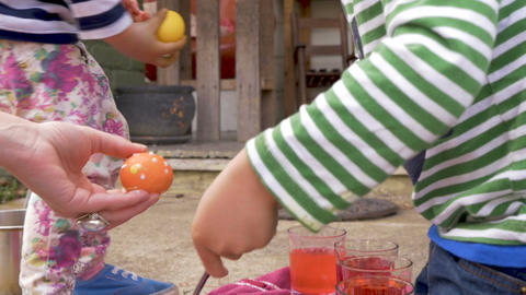 Young boy and girl siblings help their mother coloring easter eggs for the Footage
