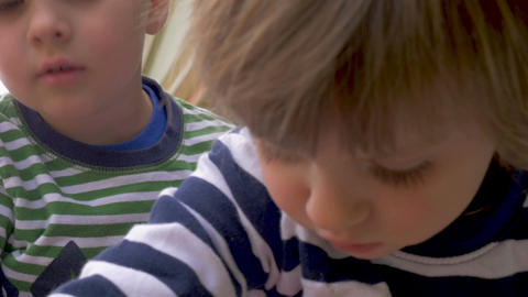 Close up of two cute young children a boy and girl focused on playing together Footage