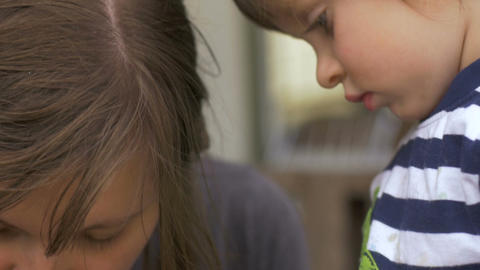 Little girl carefully watching her mother learning how to do something in slow Footage