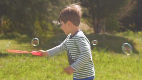 Adorable little boy spinning in circles making bubbles outside in a park on a Footage