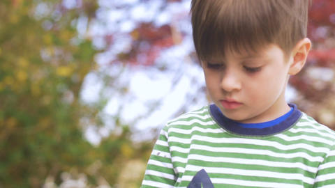 Little boy looking down focused and concentrating on something in slow motion Footage
