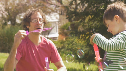Father and son blowing bubbles together outside in slow motion Footage