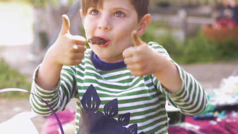 Cute little boy giving thumbs up while enjoying eating chocolate in slow motion Footage