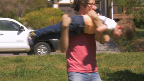 A handsome man spinning and twirling around a cute young boy outside in slow Footage