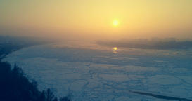 Aerial: camera flying over frozen river Danube at sunset Footage