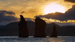 Kamchatka Peninsula seascape: Three Brothers Rocks in Pacific Ocean at sunset Footage