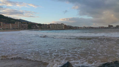Light surf in the evening in the beach,against on the city. Castro-Urdiales, Footage