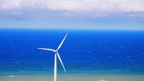 Wind turbine rotating over blue sky generating green energy. Philippines Footage