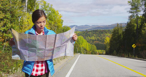 Woman looking at map on adventure nature travel by autumn landscape Footage