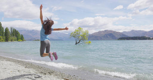 New Zealand travel happy tourist woman jumping of joy at Wanaka lake tree Footage