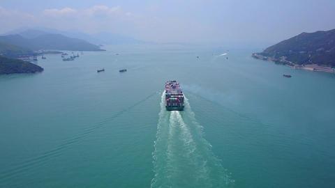 Container ship sail away at Ma Wan fairway, towards Lantau Island, aerial Footage
