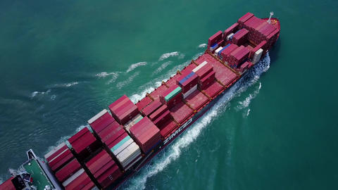 Large container vessel sail at beautiful waters, cinematic tilt-down aerial shot Footage