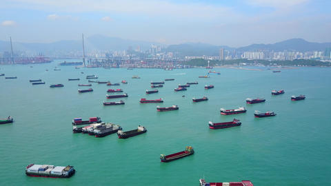 Many small container ships anchored at water area against port terminals, aerial Footage