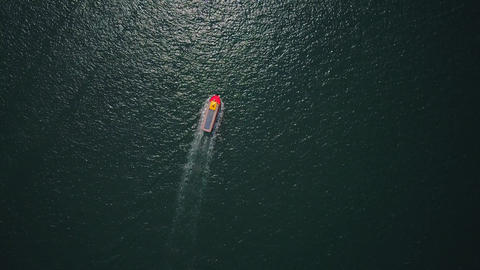 Ferry boat sail across dim green waters, top-down aerial view Footage