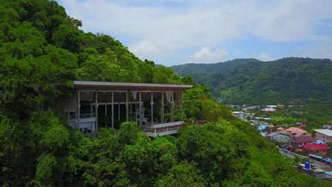 Old abandoned building on mountain slope among dense tropical forest Live Action