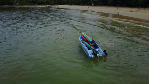 Motorboat launched to water at public beach, recreational inflatable banana Live Action