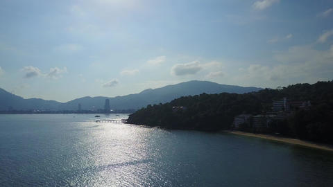 Tropical sea coast at strong backlight, dim beach and forested hill, shiny water Footage