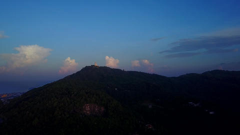 Dim forested mountains at early morning, Big Buddha statue on top, aerial shot Footage