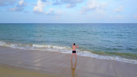 Man stay at swashing waves face to sea, twist body, stretching exercises Footage
