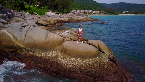 Sportive girl stay on rock, rough stony beach, camera fly towards and pass by Footage