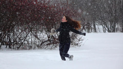 Woman turn around under snow with hat off, enjoy nice snowfall, slow motion shot Footage
