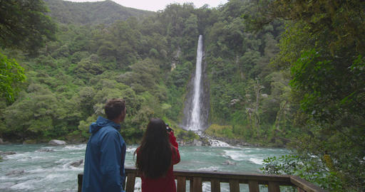New Zealand tourists at waterfall Thunder Creek Falls and Haast River landscape Footage