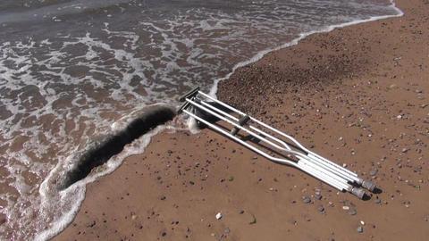 pair crutch on summer beach sand near sea Live Action