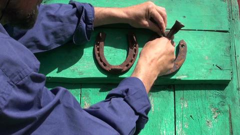 hammering rusty horseshoe luck symbols on farm door Live Action