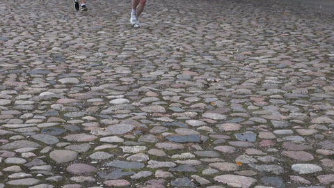 running race competing – feet on old cobblestone road Live Action