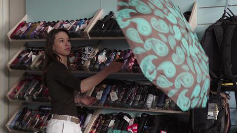 woman chooses an umbrella in shop Footage