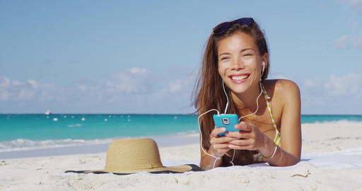 Woman listening to music wearing earphones on beach vacation singing along Footage