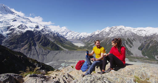 Hiking couple taking break eating food on alpine hike by Mount Cook New Zealand Live Action