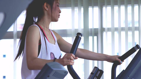 Young Woman Exercising on the Cross Trainer Machine Footage