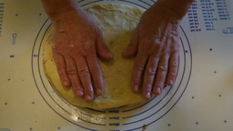 Female hands stretching a pie-like dough meal Footage