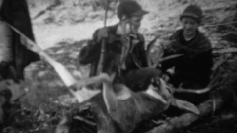 1939: Hunting couple pose with field dressed gutted whitetail deer Footage
