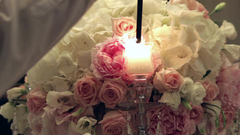 Waiter light candles of a huge bouquet of roses placed on the table of special g Footage