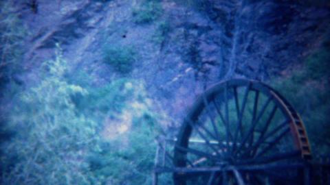 1940: Waterfall powered water wheel turning to create work Footage