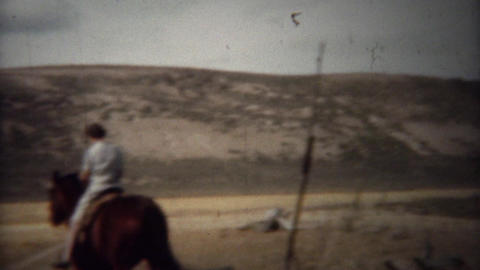 1940: Pipe smoking cowboy and wife riding horses on the range Footage