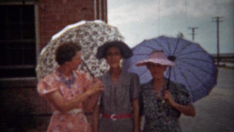 1940: Fashionable women with sun umbrellas and colorful dresses Footage
