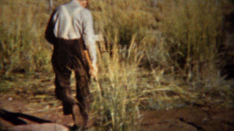 1940: Man setting up hunting blind camping tent with axe hammer Footage
