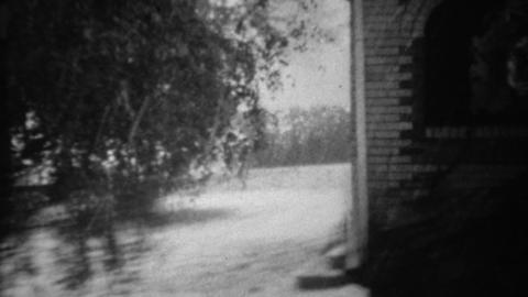 1940: Hard hail storm pouring on house and damaging classic cars Footage